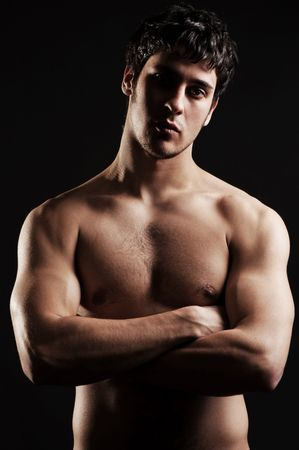 hefty: sexy man with torso posing against dark background Stock Photo