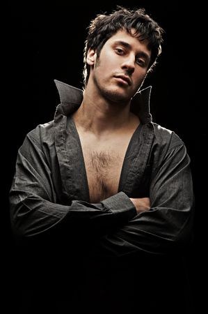 the seducer: young handsome man in shirt against black background
