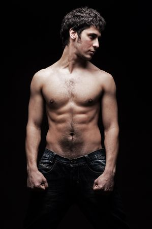 the tempter: handsome young man with torso posing against dark background Stock Photo