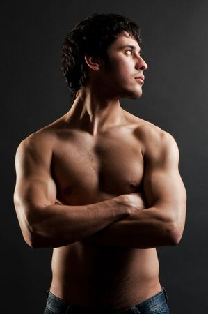handsome muscular man posing against dark background Stock Photo