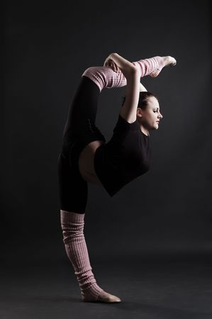 contortionist: beautiful gymnast doing splits against dark background Stock Photo