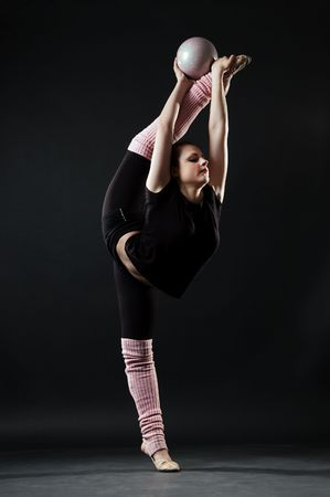 beautiful gymnast with ball against dark background photo