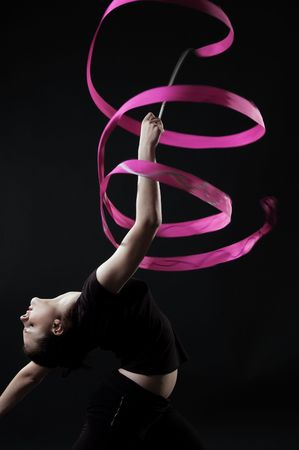 beautiful gymnast with pink ribbon against dark background photo