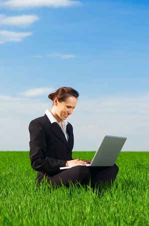 beautiful woman working with laptop at the green meadow photo