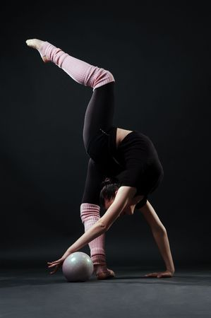 lovely gymnast with ball against dark background photo