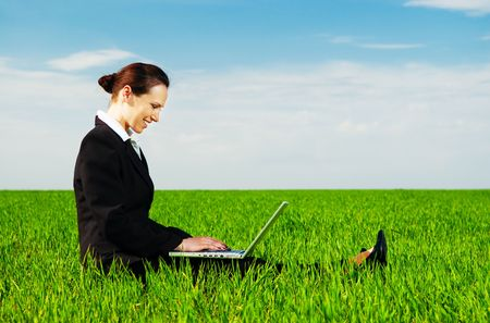 smiley businesswoman resting with laptop at the green meadow photo