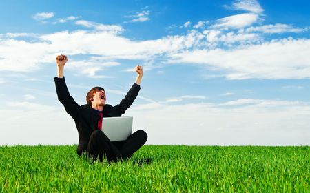 successful businessman with laptop sitting at the green grass photo