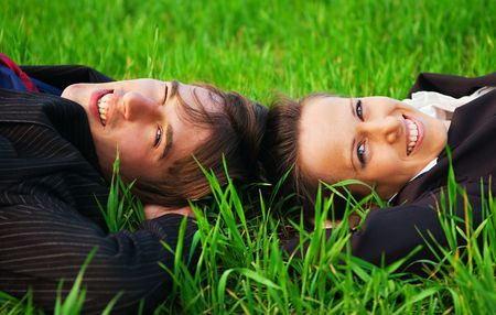 two carefree colleagues resting at the green grass photo