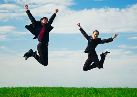 two happy colleagues jumping at the green field photo