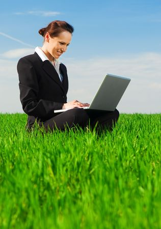 beautiful businesswoman with laptop sitting at the green grass photo