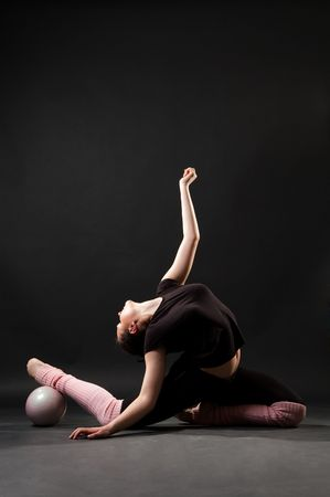 contortionist: contortionist with ball against dark background