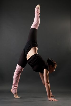 contortionist: graceful gymnast standing in splits against dark background Stock Photo