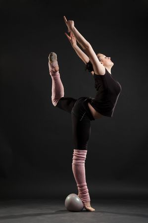 graceful flexible woman with ball against dark background photo
