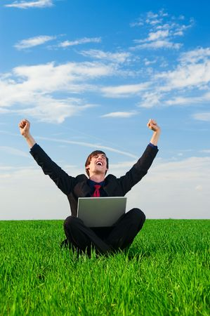 happy businessman with laptop sitting at the grass photo
