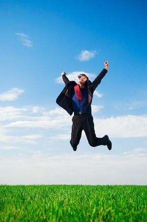 lucky businessman in jump against blue sky photo