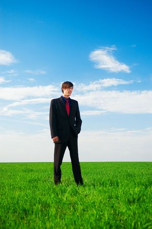 serious businessman standing at the green grass photo