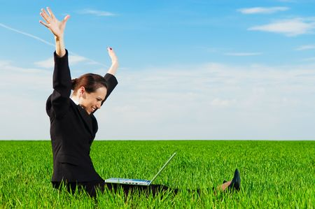 successful businesswoman with computer sitting at the green field photo