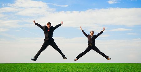 two happy colleagues in jump against blue sky photo