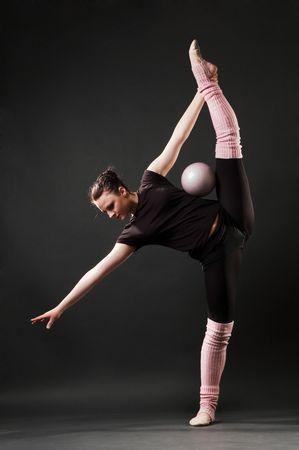 graceful dancer with ball against dark background photo