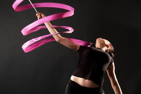 gymnast with pink ribbon dancing against dark background