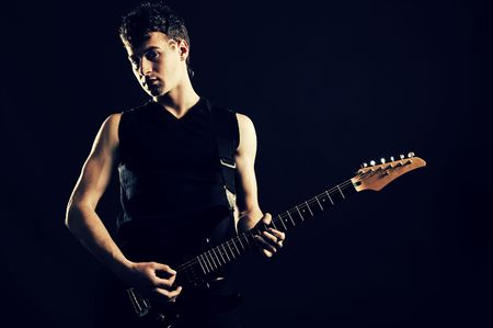 showbusiness: guitarist playing against black background