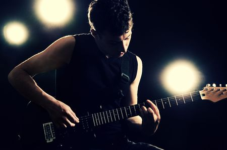 a guitarist boy playing guitar: handsome guitarist playing on the stage