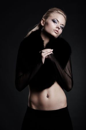 sexy woman in black fur posing against dark background photo