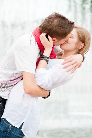 novios besandose: hermosa imagen de besar al aire libre en la mayor Foto de archivo