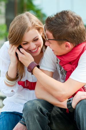 couple of happy teenagers talking on the phone Stock Photo - 5075499