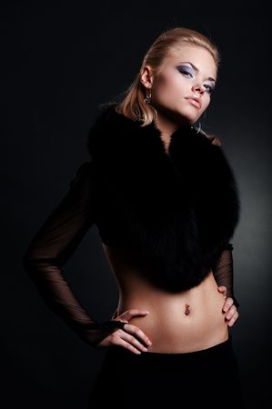 fashion model in black fur posing against dark background photo