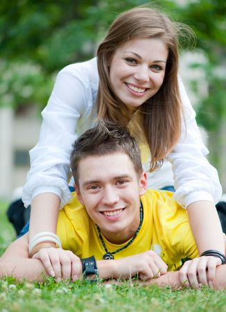 happy couple of teenagers on the grass Stock Photo - 5075443