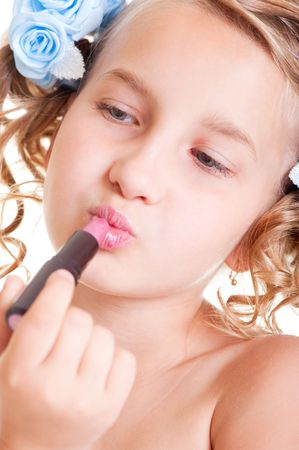 small beauty painting her lips of pink lipstick photo