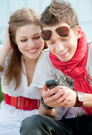 calling communication: attractive smiley teenagers looking at cellphone