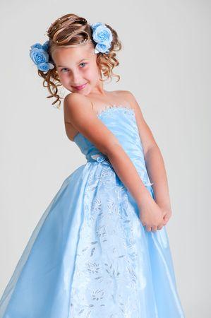 joyful little princess in blue dress posing against grey background photo