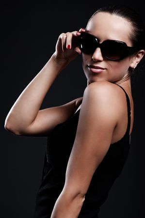 smiley beautiful woman in sunglasses posing against dark background Stock Photo - 5335664