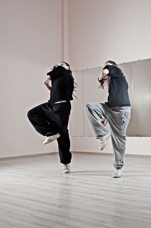 synchronously: two girls dancing synchronously in dance studio