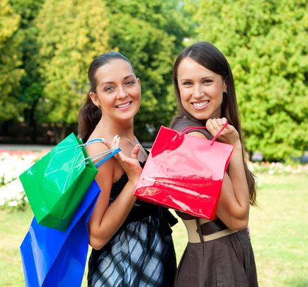 two pretty women with bags in park photo