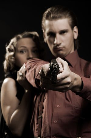 woman hiding behind the serious man with gun photo