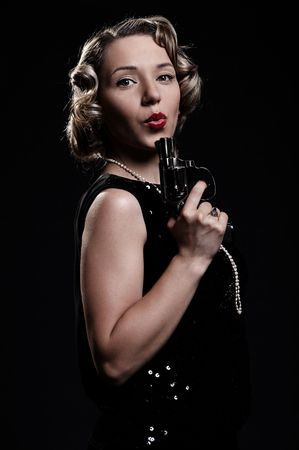 retro portrait of woman with gun against black background photo