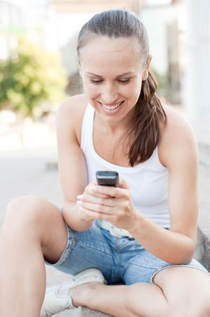 portrait of smiley young woman with cellphone photo