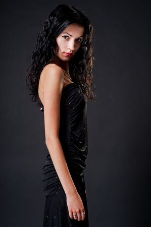 portrait of attractive young woman against dark background photo