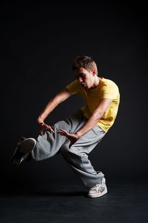 b-boy in yellow t-shirt dancing against dark background photo