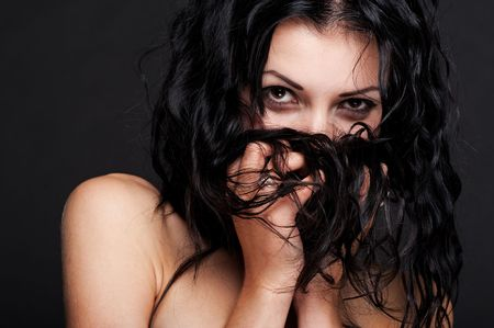 beautiful woman hiding in her hair against dark background photo