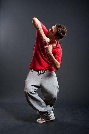 rowdy: breakdance en camiseta roja contra el fondo oscuro posando