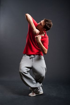 breakdancer in red t-shirt posing against dark background Stock Photo - 5530703
