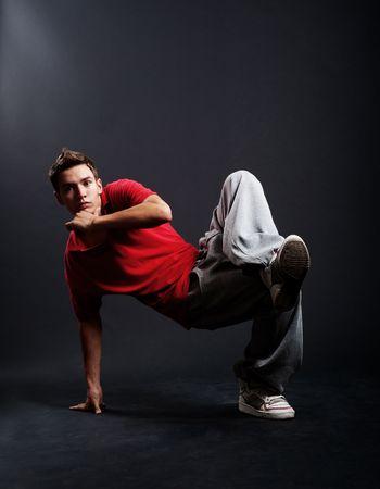 roughneck: cool breakdancer dancing against dark background Stock Photo