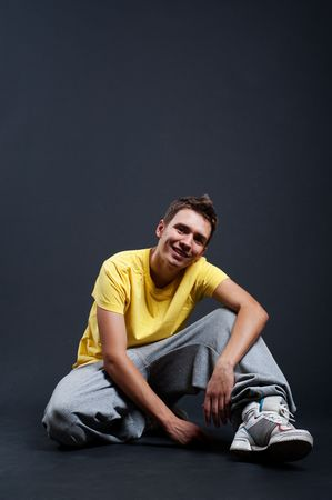 handsome smiley guy in yellow t-shirt sitting on the floor Stock Photo