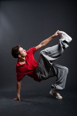 freestyle: hip-hop guy dancing against dark background Stock Photo