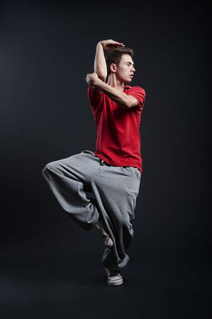 hip-hop guy in red t-shirt dancing against dark background photo