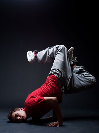 hip-hop guy standing in freeze against dark background photo